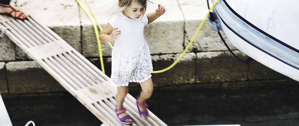 dziewczynka wchodząca na trap katamaranu